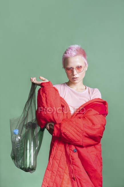 Retrato de mujer joven con el pelo corto de color rosa con abrigo rojo que sostiene la bolsa con botellas de plástico - foto de stock