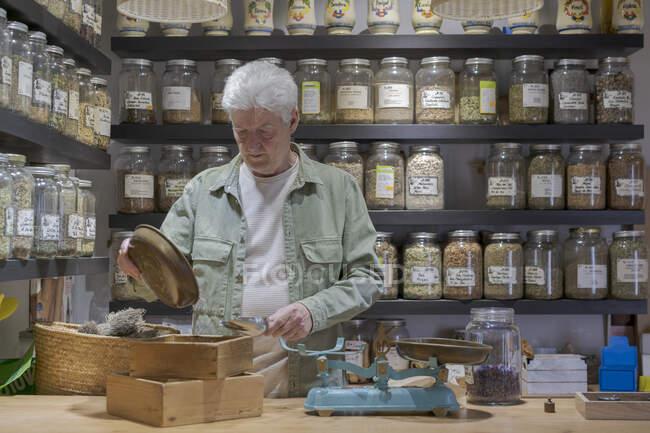 Старший человек за прилавком в своем магазине работает с весами — стоковое фото