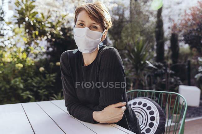 Mulher com máscara facial sentado n o jardim — Fotografia de Stock