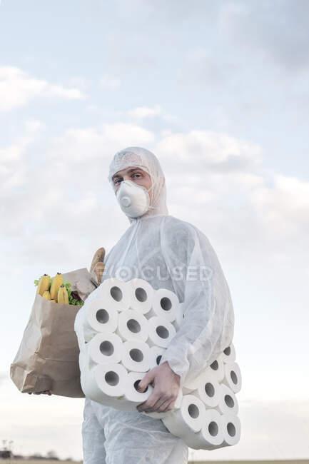 Hombre con traje protector y máscara sosteniendo rollos de inodoro y bolsa de comestibles al aire libre - foto de stock