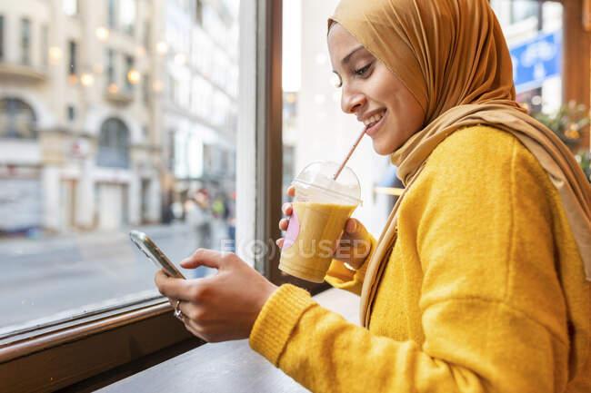 Retrato de jovem feliz com smoothie e smartphone em um café — Fotografia de Stock
