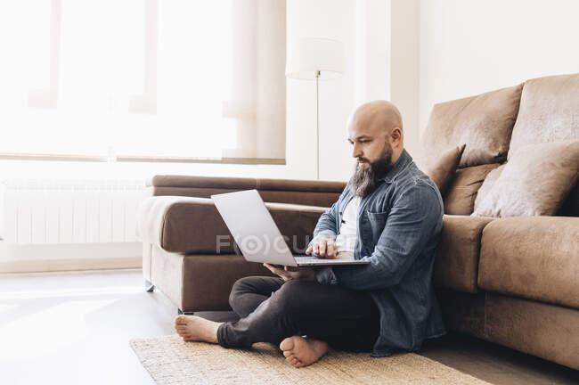 Uomo d'affari con la testa rasata che lavora sul computer portatile mentre seduto sul pavimento contro il divano a casa — Foto stock