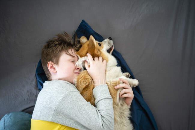 Retrato de niño acostado en la cama abrazando a su perro - foto de stock