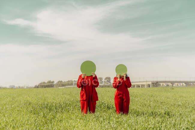 Pareja joven vestida con monos rojos de pie en un campo escondiendo caras detrás de círculo verde - foto de stock
