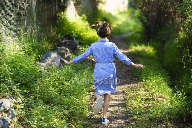 Дівчинка біжить сільською стежкою. — стокове фото