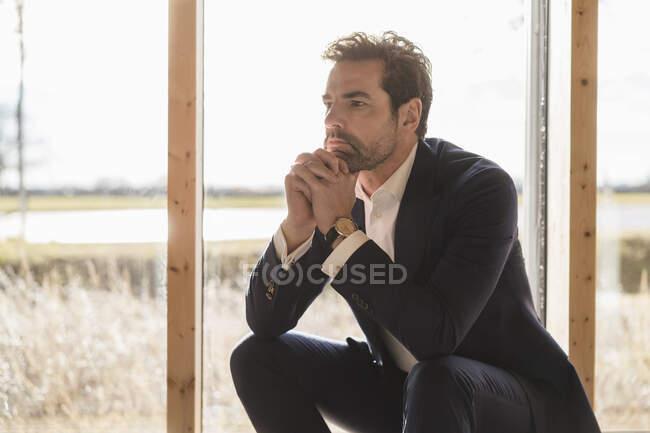 Серйозний бізнесмен сидить біля вікна в офісі. — стокове фото