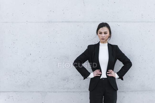 Mujer joven vistiendo traje negro de pie frente a la pared de hormigón - foto de stock