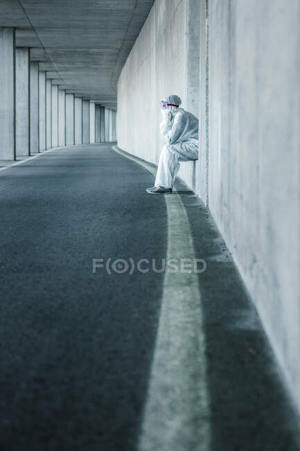Exhausted man wearing protective clothing sitting in a niche of a concrete wall in a tunnel — Stock Photo