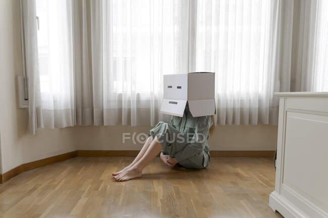 Mujer con una caja de cartón en la cabeza con sonrisa aburrida y sentada en el suelo en casa - foto de stock