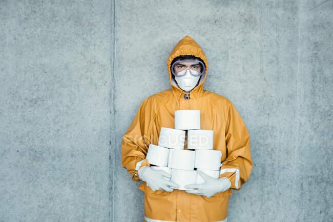 Retrato de homem vestindo roupas protetoras segurando rolos de banheiro — Fotografia de Stock