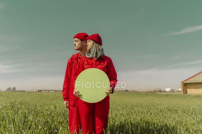 Pareja joven vestida con monos rojos y sombreros de pie en un campo con círculo verde - foto de stock