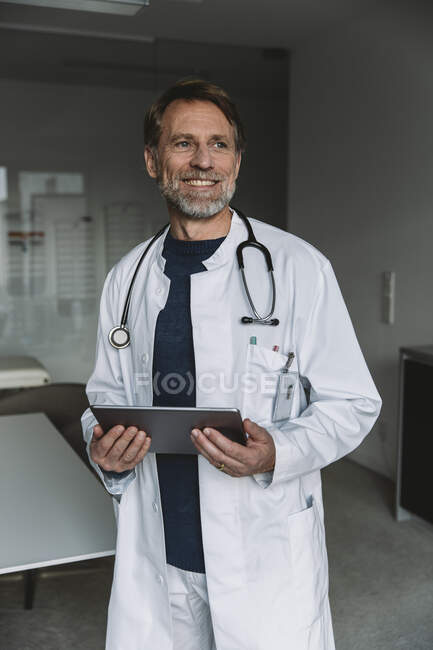 Retrato del médico sonriente sosteniendo la tableta - foto de stock