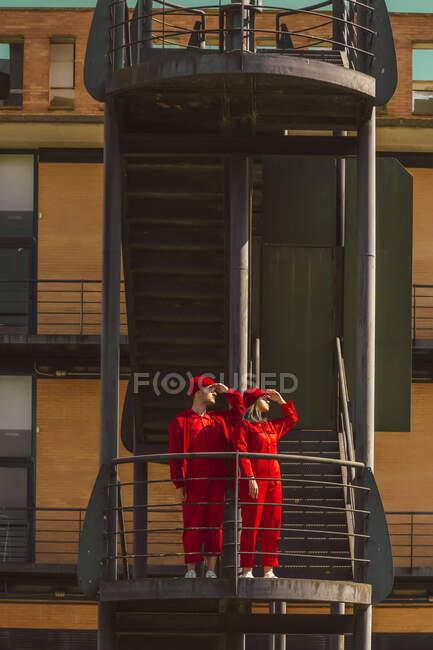 Pareja joven vestida con monos rojos y sombreros de pie en la plataforma mirando a la distancia - foto de stock