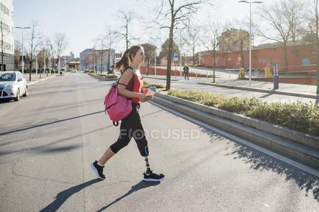 Mujer joven deportiva con prótesis de pierna caminando por la ciudad - foto de stock