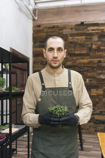 Портрет уверенного человека с микрозеленым растением — стоковое фото