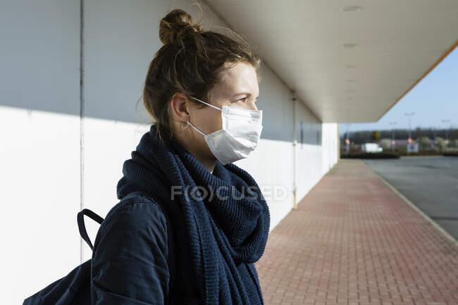 Retrato de mujer con máscara en una calle vacía - foto de stock