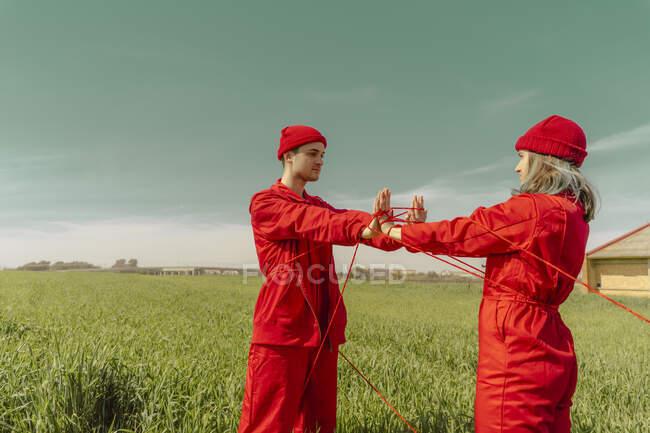 Pareja joven vestida con monos rojos y sombreros actuando en un campo con hilo rojo - foto de stock