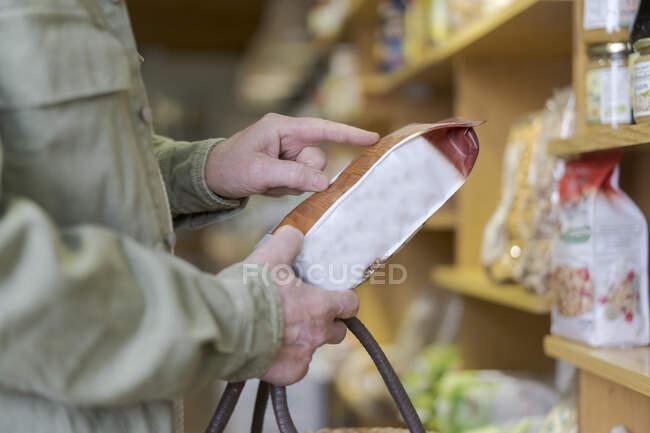Крупный план пожилого человека, покупающего продукты в небольшом продуктовом магазине, проверяющего ингредиенты — стоковое фото
