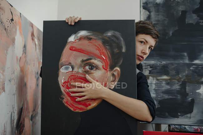 Портрет художниці з живописом у своїй майстерні. — стокове фото