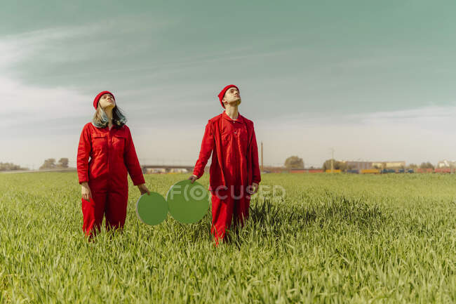 Pareja joven con monos rojos de pie en un campo con dos círculos verdes mirando hacia arriba - foto de stock