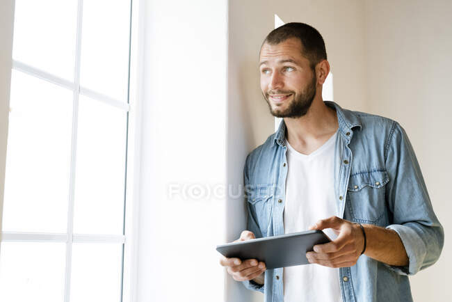 Young smiling man at home holding his tablet and looking outside of his window — Stock Photo
