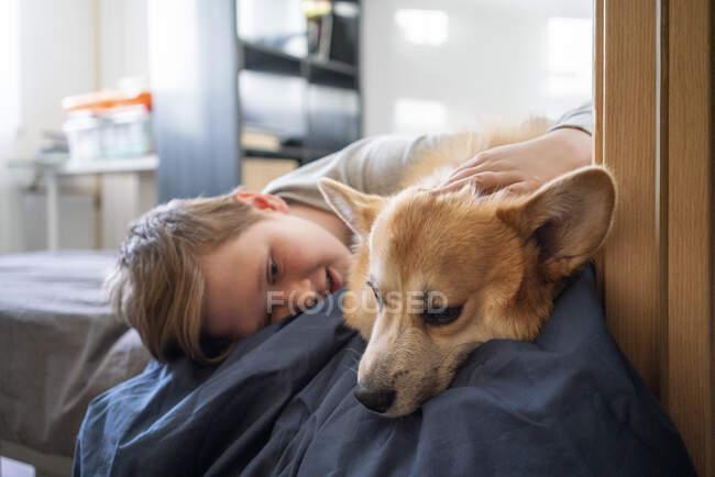 Chico acostado en la cama acariciando a su perro - foto de stock