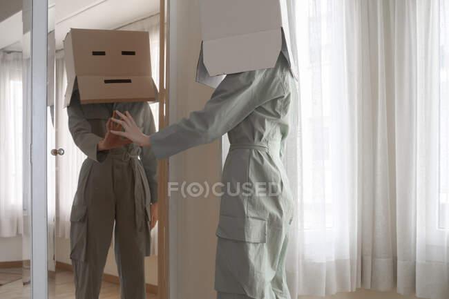 Mujer con una caja de cartón en la cabeza con aburrido espejo táctil sonriente - foto de stock