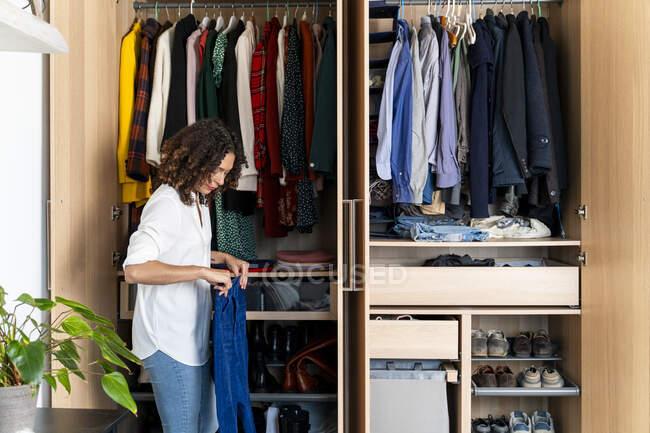 Mulher limpando seu guarda-roupa — Fotografia de Stock