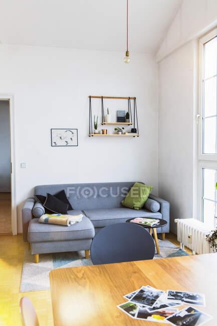 Fotografie su tavolo in luminoso soggiorno con grandi finestre — Foto stock