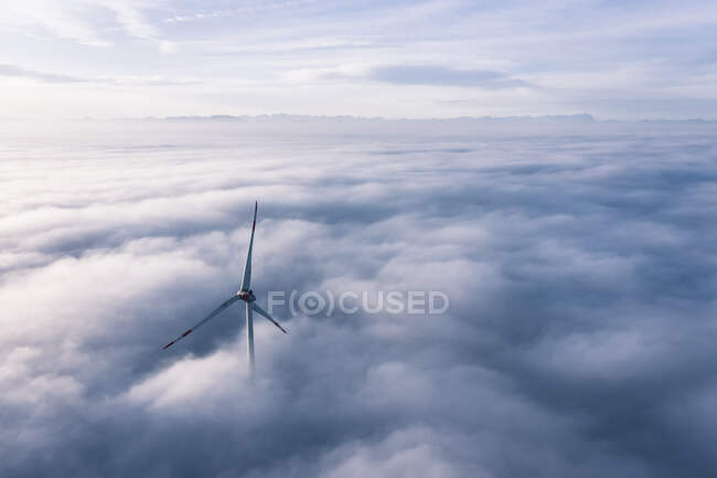Germany, Aerial view of wind turbine shrouded in clouds at dawn — Stock Photo