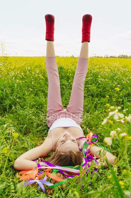 Девушка в красных сапогах на цветочном лугу весной — стоковое фото