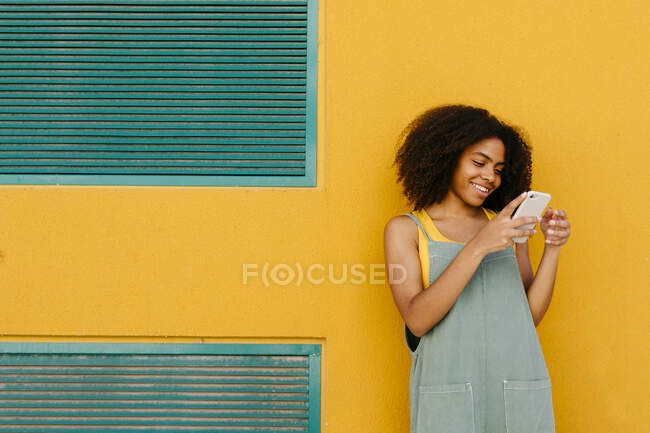 Smiling young woman wearing overalls in front of yellow wall using smartphone — Stock Photo