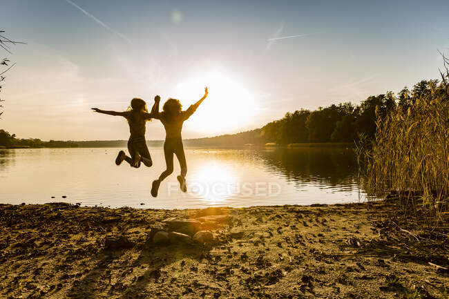 Freunde springen bei Sonnenuntergang am Seeufer in der Luft gegen den Himmel — Stockfoto