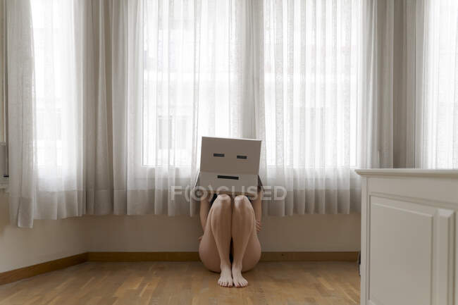 Mujer con una caja de cartón en la cabeza con sonrisa aburrida y sentada en el suelo - foto de stock