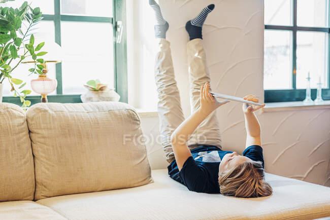 Мальчик лежит на диване в гостиной дома с помощью планшета — стоковое фото