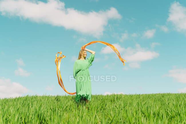 Glückliche junge Frau in einem grünen Kleid auf einem Feld mit wehenden Bändern — Stockfoto