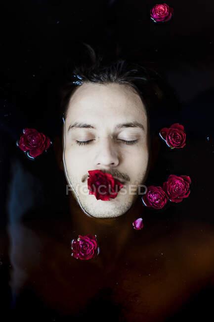 Портрет молодого человека с красной розой во рту, плавающего в воде — стоковое фото