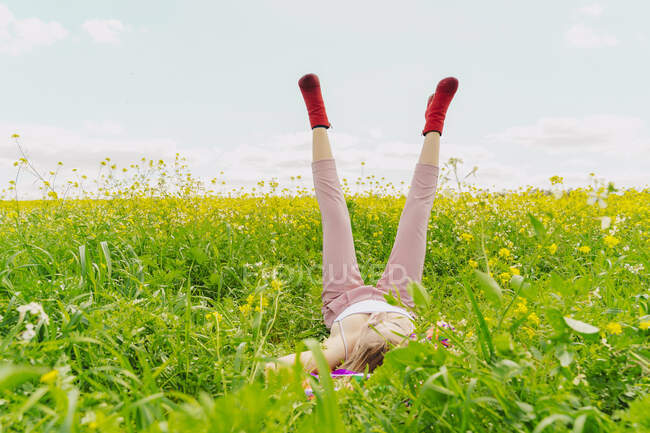 Young woman wearing red ankle boots lying in a flower meadow in spring — стокове фото