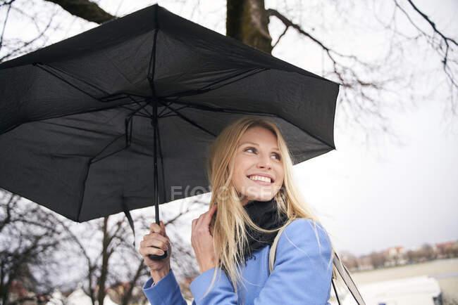 Femme blonde souriante tenant un parapluie à l'extérieur — Photo de stock