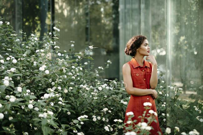 Pensive jovem mulher de pé no jardim urbano — Fotografia de Stock