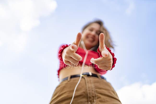 Wurms Blick auf junge Frau, die mit Kopfhörern Musik hört — Stockfoto