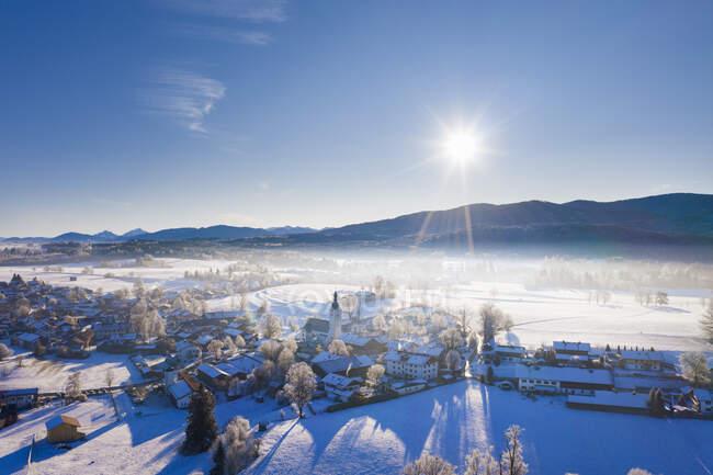 Germania, Baviera, Reichersbeuern, Drone vista del sole che splende sul villaggio innevato — Foto stock