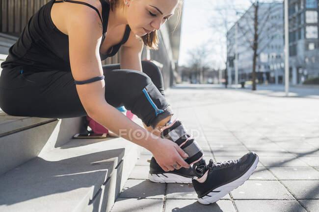 Спортивная молодая женщина с протезом ноги сидит на лестнице в городе — стоковое фото
