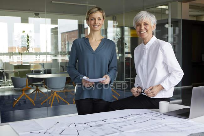 Портрет двох довірливих підприємців з планом будівництва. — стокове фото