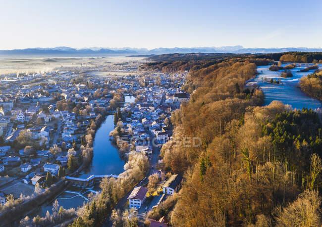 Alemania, Baviera, Wolfratshausen, Drone vista de la ciudad en las estribaciones alpinas en el amanecer de invierno - foto de stock