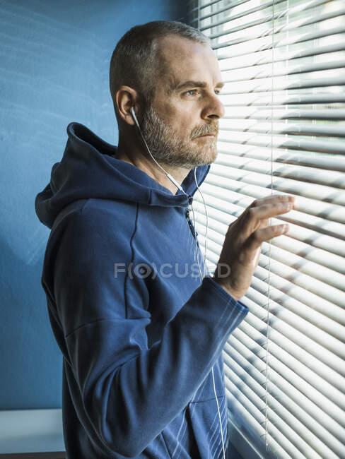 Hombre pensativo con auriculares mirando por la ventana veneciana ciega - foto de stock