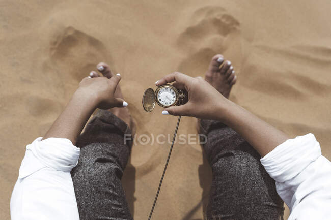Рука жінки тримає старий кишеньковий годинник, пустеля Мерзуґа, Марокко. — стокове фото