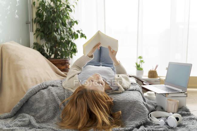 Jovem mulher lendo notebook em casa — Fotografia de Stock