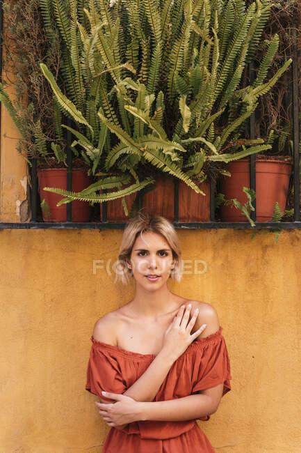 Портрет молодої жінки, що стоїть перед жовтою стіною. — стокове фото