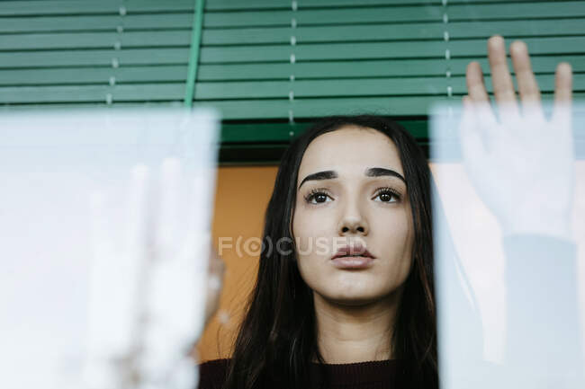 Retrato de una joven seria detrás del cristal de la ventana mirando a la distancia - foto de stock